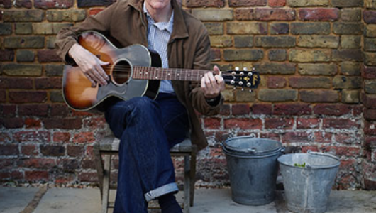 Nick Lowe with guitar in front of brick wall
